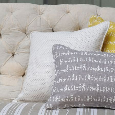 Cloth and Clover -  Cloth and Clover Collection - A sofa with a cream padded back, a striped grey seat,and two grey and white cushions featuring dots and a fun print