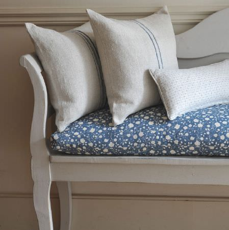 Cloth and Clover -  Cloth and Clover Collection - A white bench with a navy and white floral patterned seat cushion, and 3 grey-white and blue striped and dotted cushions