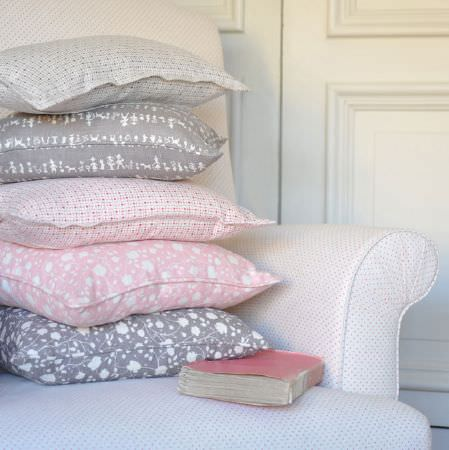Cloth and Clover -  Cloth and Clover Collection - A white armchair with tiny dots, with 5 scatter cushions featuring patterns in white and pale shades of pink and grey
