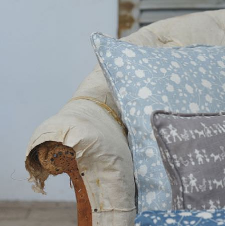 Cloth and Clover -  Cloth and Clover Collection - A distressed cream sofa with fabric which is coming undone, with light blue, grey and white floral and patterned cushions
