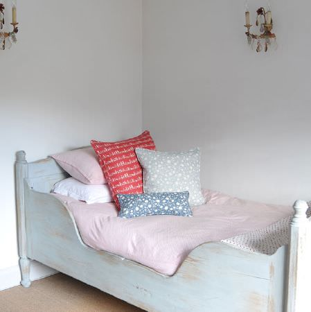 Cloth and Clover -  Cloth and Clover Collection - A wooden cot style bedframe painted white, with plain pastel pink bedding, and red, blue, grey and white patterned cushions