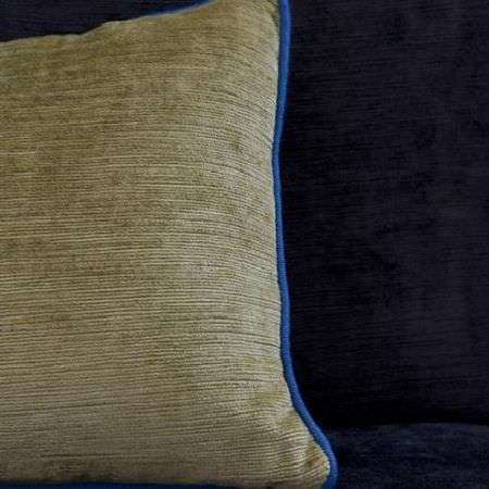 Design Forum -  Cognac Fabric Collection - Olive green cushion with bright blue piping against a dark indigo fabric background