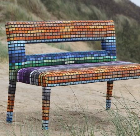 Design Forum -  Kaleidoscope Fabric Collection - Bench covered in multicoloured squares resembling a mosaic, with a cut-out in the backrest