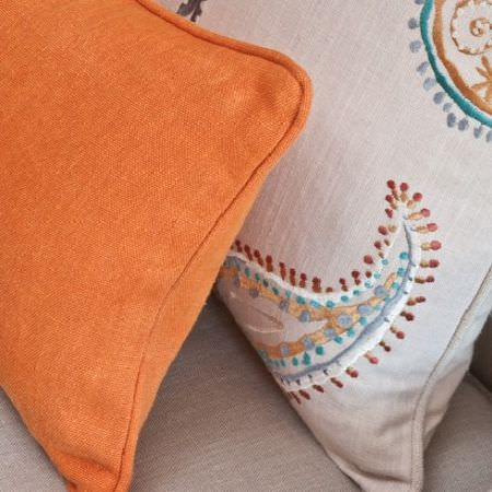 Design Forum -  Pluto Fabric Collection - Bright orange cushion and a cream cushion with a white, blue, gold and bronze embroidered paisley design