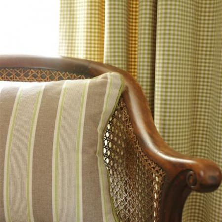 Design Forum -  Rimini Fabric Collection - Wood and wicker woven chair, with a beige, cream and green striped cushion, and green and cream checked curtains