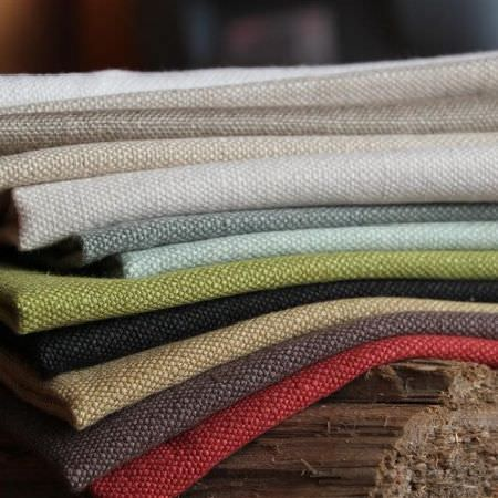Design Forum -  Swiss Linen Fabric Collection - Stack of strong fabrics in a range of eleven different colours