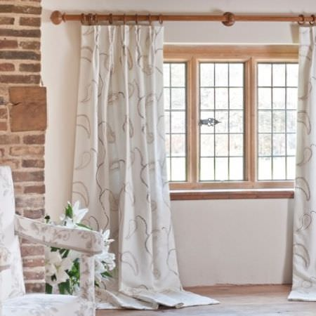 Design Forum -  Tuscany Fabric Collection - Cream curtains with a large grey paisley pattern, and a white and grey floral armchair