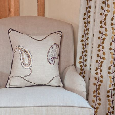 Design Forum -  Tuscany Fabric Collection - Plain cream armchair, a plain cream cushion with white, gold and black paisley design,and cream fabric with embroidered rows of gold leaves