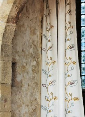 Design Forum -  Umbria Fabric Collection - Long cream fabric curtains with a vertical design of leaves and vines made up of solid gold, blue and green lines