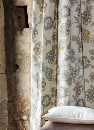 Design Forum -  Umbria Fabric Collection - Grey florals as a large print pattern on long, off-white coloured fabric curtains, with two cushions; one brown-grey and one off-white
