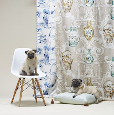 Edinburgh Weavers -  Eastern Empire Fabric Collection - Two pugs on a plain cushion and a white chair, with two patterned fabrics in blue and white, andbeige, gold and green