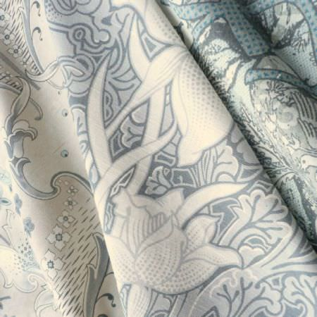 Edinburgh Weavers -  Faded Elegance Fabric Collection - Folds of fabric featuring very similar busy patterns in slightly different cream, light grey and duck egg blue colours