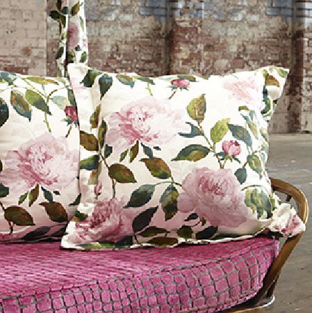 Edinburgh Weavers -  Hidden Secrets Fabric Collection - Large cushions in white, printed with big pink flowers and dark green leaves, on a wooden bench with a textured pink and grey seat cushion
