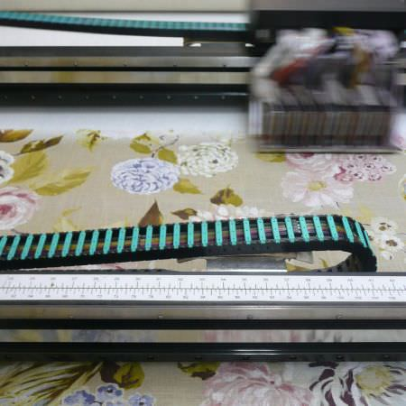 Edinburgh Weavers -  New Designs Fabric Collection - A floral pattern in shades of green, pink and blue being printed onto plain white fabric