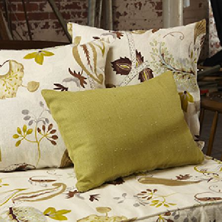 Edinburgh Weavers -  Nouveau Fabric Collection - A rectangular olive green scatter cushion with seat and scatter cushions in cream patterned with flowers and leaves in green, grey and brown