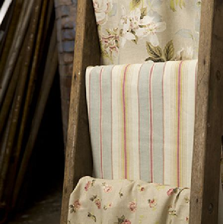 Edinburgh Weavers -  Persuasion Fabric Collection - Wooden ladder with fabrics hung on the rungs; one dusky blue, cream and red striped, and two floral prints in green, cream, grey and pink
