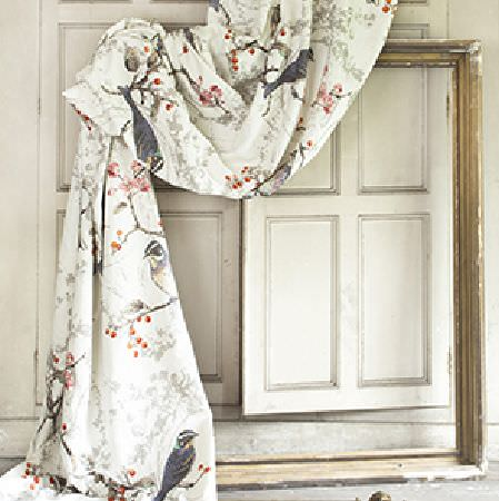 Edinburgh Weavers -  Wonderland Fabric Collection - Distressed gold frame draped with cream coloured fabric which has a red berry, grey branch and black bird pattern printed on it