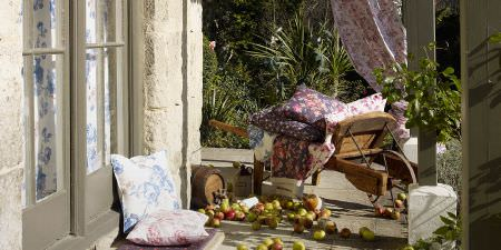 Elanbach -  In The Country Fabric Collection - Wooden wheelbarrow stacked with different colour floral cushions, beside a wooden barrel, pink, blue and white floral cushions and curtains