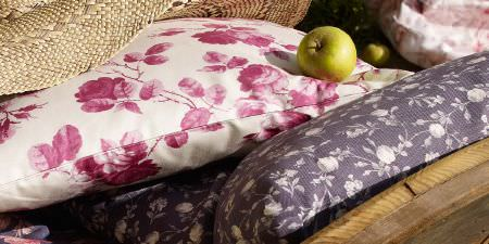 Elanbach -  In The Country Fabric Collection - Floral print cushions in designs featuring pink and white, and purple and white, next to wood and burlap effect fabric