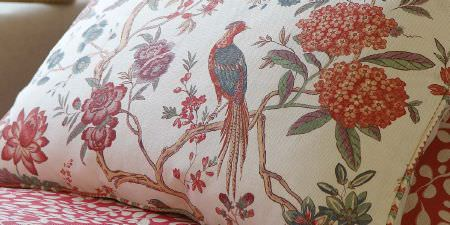 Elanbach -  In The Country Fabric Collection - Cushion decorated with flowers, branches and birds in dusky red, blue and brown tones, next to red and white patterned fabric