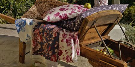 Elanbach -  In The Country Fabric Collection - White, blue, pink and purple flowered fabrics and cushions in a wooden wheelbarrow
