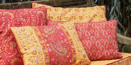 Elanbach -  Spice Route Fabric Collection - Cushions with yellow and salmon coloured floral and paisley prints, on a wooden bench