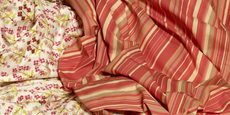 Elanbach -  Spice Route Fabric Collection - Fabric with salmon, cream and terracotta stripes in differing widths, next to cream fabric with a small pink and green floral print