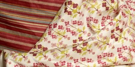 Elanbach -  Spice Route Fabric Collection - Tiny pink and purple flowers and green leaves on off-white fabric, beside a thick fabric with deep red, pink, beige, green and blue stripes