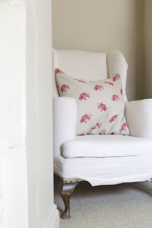 Emily Bond -  Country Fabric Collection - Red and putty coloured patterned square scatter cushion on a plain cream padded armchair with feet made from dark brown wood