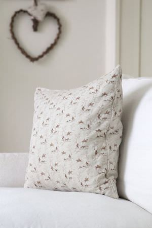 Emily Bond -  Country Fabric Collection - A milky white padded chair beneath an off-white coloured cushion which has a tiny dark red pattern, beside a brown heart shaped wall hanging