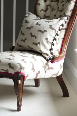 Emily Bond -  Dogs Fabric Collection - Padded chair with a low seat, dark wood legs and upholstered with cream fabric covered in brown dogs, with a matching cushion with pom-poms