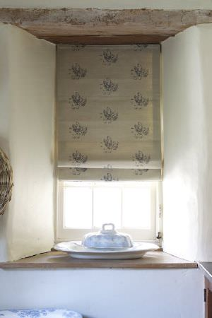 Emily Bond -  Farmyard Fabric Collection - Narrow beige coloured window blinds with a repeated light grey pattern arranged in neat rows, hanging above a white butter dish