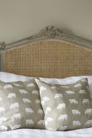 Emily Bond -  Farmyard Fabric Collection - Wicker headboard with a grey ornate wood frame, with plain white bedding and two light brown cushions, both printed with rows of white cows