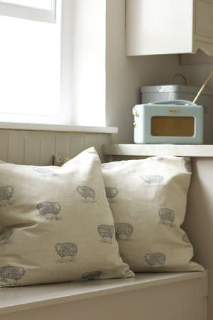 Emily Bond -  Farmyard Fabric Collection - Light grey sheep printed at wide intervals over cream coloured scatter cushions, beside a vintage style radio
