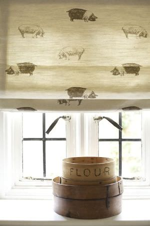 Emily Bond -  Farmyard Fabric Collection - Pig print window blinds in shades of cream, beige and grey, above a container for storing flour