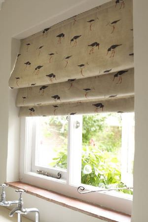 Emily Bond -  Seaside Fabric Collection - Black, white and orange wading birds arranged in rows over beige coloured wide window blinds