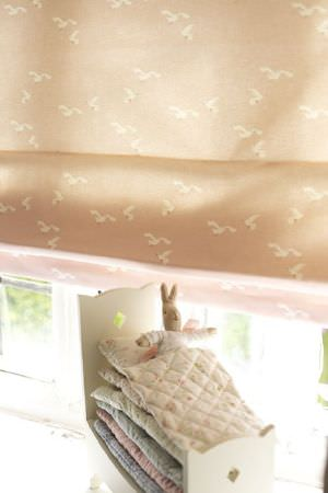 Emily Bond -  Seaside Fabric Collection - Caramel coloured window blinds covered with cream birds, with a toy rabbit in a toy bed which is stacked with six tiny duvets and pillows