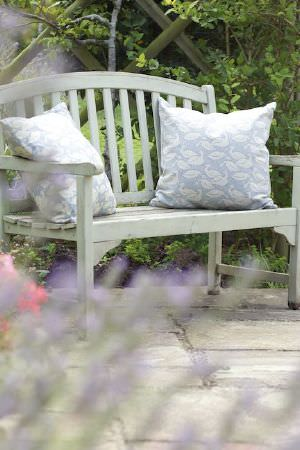 Emily Bond -  Seaside Fabric Collection - Light green painted wooden bench, with two light blue coloured swan print scatter cushions, both with a white pattern