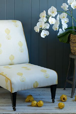 Emily Bond -  Vegetables And Fruit Fabric Collection - Interesting upholstered armchair dyed in white decorated with a pattern of yellow fruits and vegetables