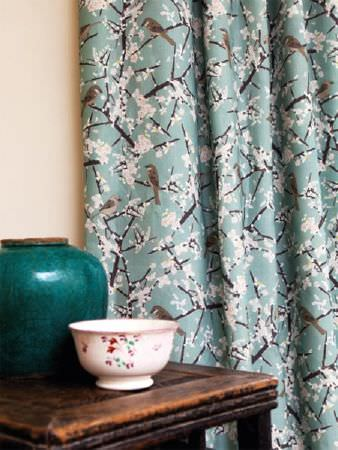 Emily Burningham -  Emily Burningham Fabric Collection - Curtain with blue background with dark branches, white blossom and birds, japonaise style.