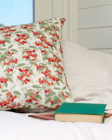 Emily Burningham -  Emily Burningham Fabric Collection - Cushion with cream background with orange berries and leaves in shades of green.