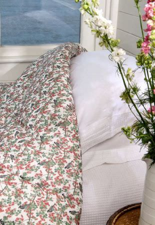 Emily Burningham -  Emily Burningham Fabric Collection - Quilt with mottled floral pattern in reds and greens on self-striped white sheets and pillow case.