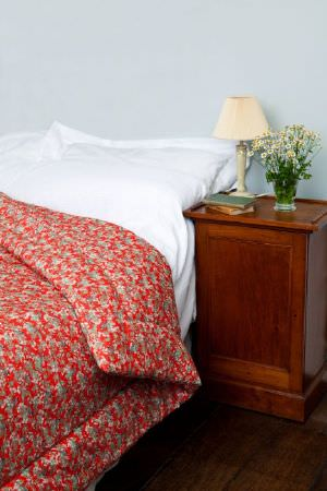 Emily Burningham -  Emily Burningham Fabric Collection - Quilt in shades of mottled red and green an dplain white sheet.