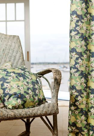 Emily Burningham -  Emily Burningham Fabric Collection - Curtains in shades of green with daisy effect pattern and matching cushion.