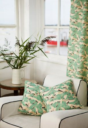 Emily Burningham -  Emily Burningham Fabric Collection - Curtains with mottled pattern of greenm cream and brown and matching cushion. Armchair in neutral with dark piping.