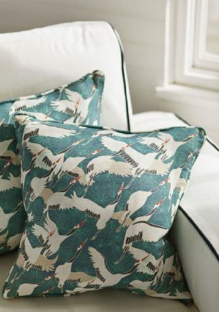 Emily Burningham -  Emily Burningham Fabric Collection - Armchair in neutral with dark piping and cushions with sea green background with splashes of white bird-like shapes and piped edging.