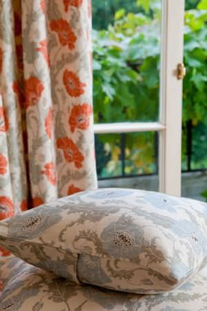 Emily Burningham -  Emily Burningham Fabric Collection - Curtains with cream background depicting red poppies and green leaves. Cushions with cream backgound and grey-blue floral effect pattern.