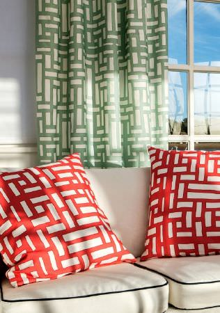 Emily Burningham -  Emily Burningham Fabric Collection - Curtains with white background and green geometric pattern. Cushions with white background and red geometric pattern.