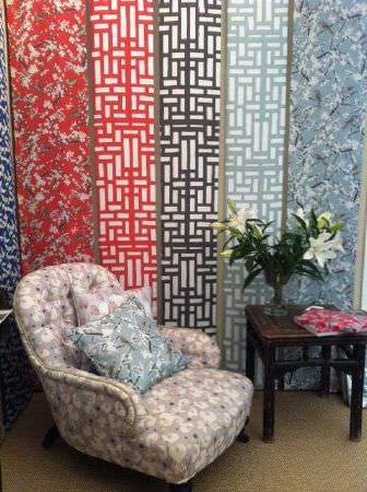 Emily Burningham -  Emily Burningham Fabric Collection - Swatches of fabric in red, black and grey geometric pattern and in shades of mottled blue. Chair in mottled pink floral, cushion in blue.