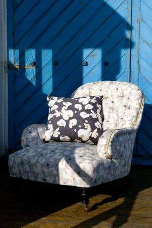 Emily Burningham -  Emily Burningham Fabric Collection - Occasional chair in light beige mottled effect fabric with cushion in dark background with large white flowers with yellow centres.